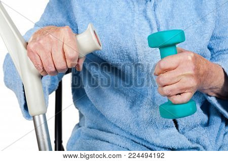 Close up picture of old disabled lady holding a blue dumbell and crutch on isolated background