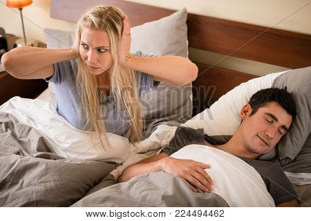 Young woman annoyed by the snoring of her partner sleeping in bed at night