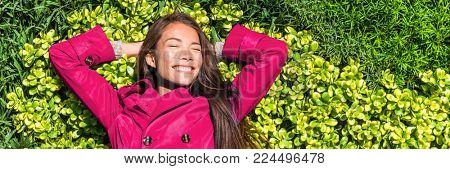 Happy woman relaxing on green spring grass banner. Header of smiling girl lying down enjoying sun