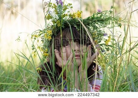 Portrait of beautiful little girl with a colorful garlang on her head and hands under her chin in high green grass on a meadow. Close shot.