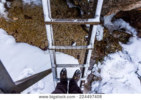 Outdoor ladder in national park Janosikove Diery. Tourist shoes on the ladder. Snow and winter.