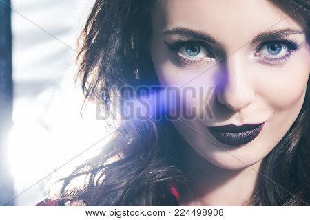 headshot of beautiful girl with dark lips looking at camera