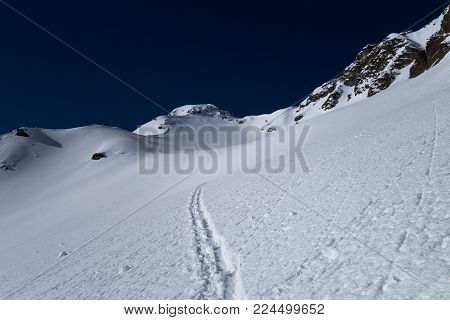 A Track Made Over New Untouched Powder Snow Leading Across Snow Field Towards Alpine Mountain Pass O