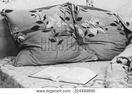 open book on a straightened bed close up, black and white photo