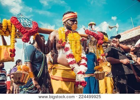 BATU CAVES, SELANGOR, MALAYSIA - 31 JANUARY 2018 Hindu devotees celebrate Thaipusam festival with procession and offerings. People portrait. Culture and traditions. Asia travel. Kavadi milk pots