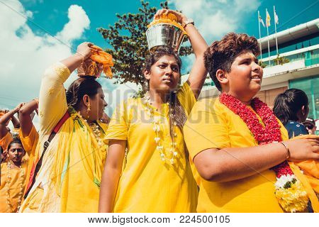 BATU CAVES, SELANGOR, MALAYSIA - 31 JANUARY 2018 Hindu devotees celebrate Thaipusam festival with procession and offerings. People portrait. Religion concept. Asian Culture and traditions. Yellow mood