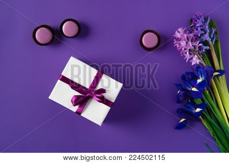 top view of present box and yummy macarons on purple poster