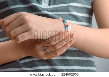 Horizontal toned shot of a female hand wearing braided bracelets. Fenichka at hand.