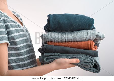 Horizontal shot of a young woman holding a pile of clothes, isolated on white background. Side view