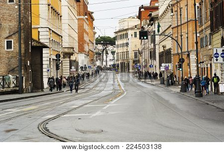 Rome, Italy, march 2015: view of Via delle Botteghe Oscure in Rome with the tram rails and people walking on a rainy day