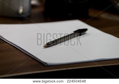 A black ball point pen on a white piece of paper