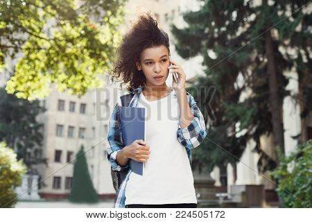 Serious african-american student girl talking on mobile at university building background. Woman with backpack and workbooks having important call. Technology, education, leisure concept