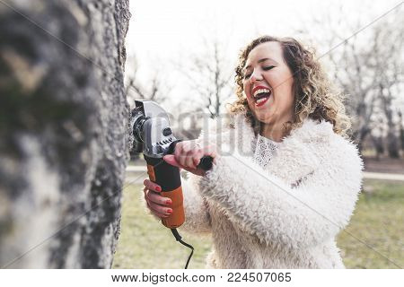 Beautiful curly woman wearing fur coat and posing an angle grinder at park. International Woman's Day concept