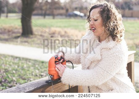 Beautiful curly woman wearing fur coat and use a jigsaw at park. International Woman's Day concept
