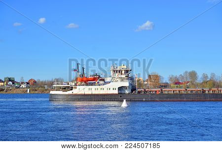 Cargo ship on the Neva river, outskirts of St.Petersburg at cloud day, Russia.