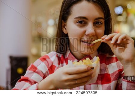 young woman eat French fries hold in hand in fron of face