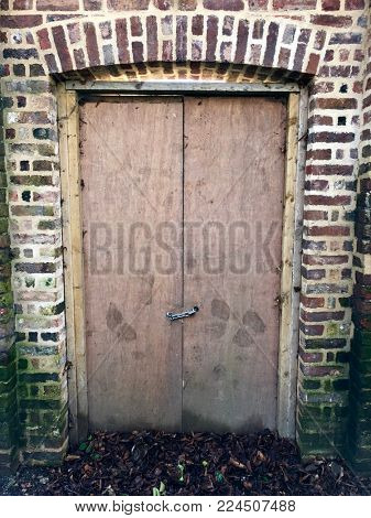 Ramshackle temporary chained wooden door inside brick wall doorway