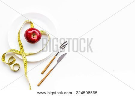 Proper nutrition for lose weight. Empty plate, apple and measuring tape on white background top view.