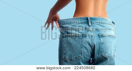Woman in oversize jeans after weight loss. Female bottom in oversize jeans on pastel blue background