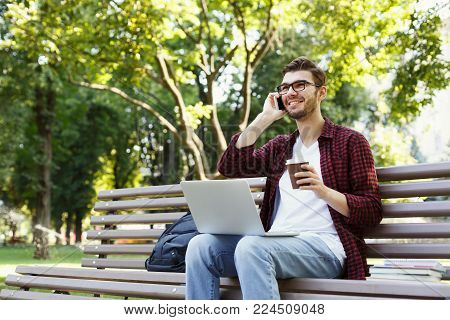 Smiling young man talking on mobile, working on laptop and having coffee, sitting in park on bench. Technology, communication, education and remote working concept, copy space