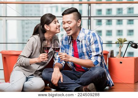 Young lovers after moving in to new city apartment having after work glass of wine