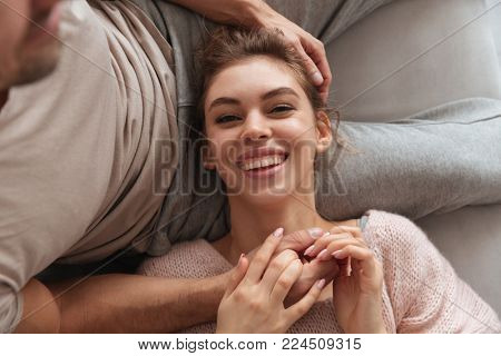 Top view of a laughing woman lying on her boyfriends lap on a couch at home