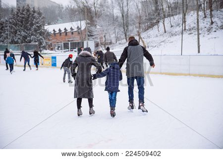 people ski at outside ice rink at winter day