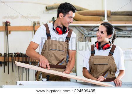 Carpenter and apprentice working together in wood workshop