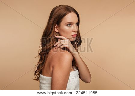 Beauty portrait of mystery ginger woman with long hair wrapped in towel posing sideways and looking away over cream background