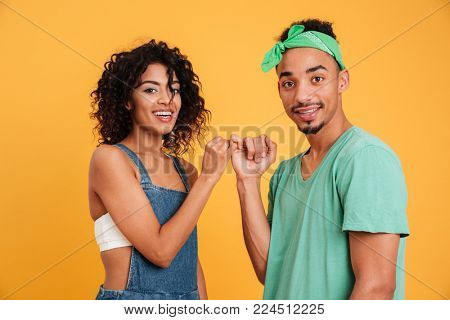 Portrait of a happy young african couple dressed in summer clothes holding pinkies isolated over yellow background