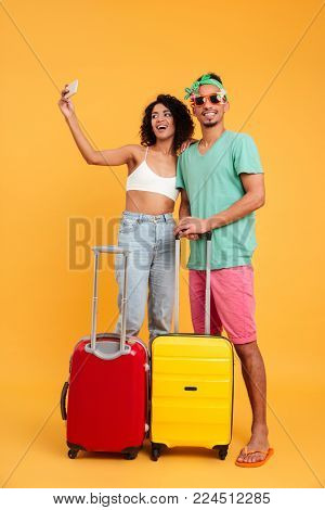 Full length portrait of a happy young african couple in summer clothes taking a selfie while standing with suitcases isolated over yellow background