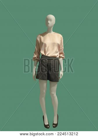 Full-length female mannequin dressed in pink blouse and shorts, isolated on green background. No brand names or copyright objects.