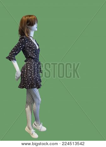 Full-length female mannequin wearing polka dot dress, isolated on green background. No brand names or copyright objects.