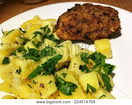 Potatoes with parsley and ground beef meat cutlet for one