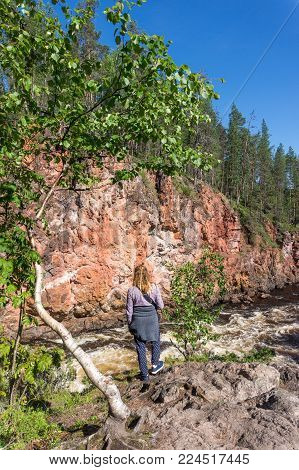 Girl standing on a rock above a stormy river, Finland. Oulanka National Park