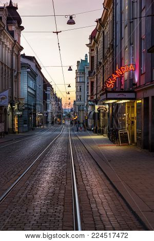 NORRKOPING, SWEDEN - AUGUST 22, 2015: Perspective evening view of a cobblestone city street with tram tracks and surrounding buildings in Norrkoping August 22, 2015. Neon signs and incidental people walking by.