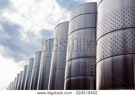 Modern technological industrial equipment of wine factory. Large stainless steel wine distilling vats on sky background.