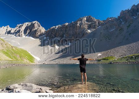 Hiker relaxing at high altitude blue lake in idyllic uncontaminated environment once covered by glaciers. Summer adventures and exploration on the Italian French Alps. Clear blue sky.