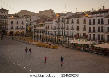 CACERES, SPAIN - DECEMBER 21, 2017: Sunset scene of the Plaza Mayor (main square), with local businesses, locals and visitors, in Caceres, Extremadura, Spain