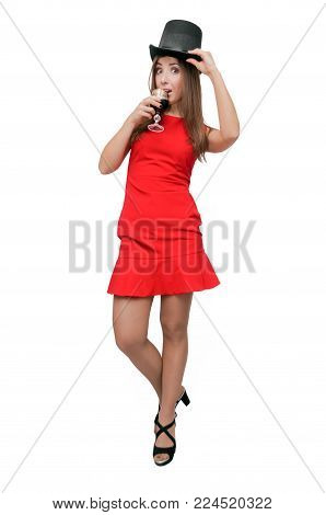 Party time. Smiling woman is holding in hands a wine glass and takes off her bowler hat isolated on dark background. Degustation of wine.