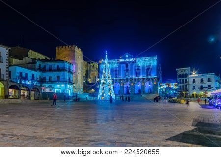 CACERES, SPAIN - DECEMBER 21, 2017: Night scene of the Plaza Mayor (main square), with various Christmas decorations, local businesses, locals and visitors, in Caceres, Extremadura, Spain