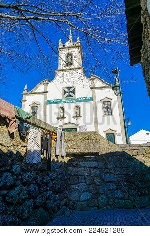 BELMONTE, PORTUGAL - DECEMBER 22, 2017: The Igreja Matriz de Belmonte church, and an alley with laundry, in Belmonte, Castelo Branco, Portugal