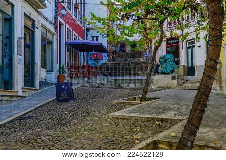 COIMBRA, PORTUGAL - DECEMBER 23, 2017: Old city street with locals and visitors, in Coimbra, Portugal