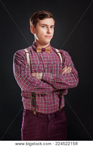 Portrait of young handsome suspicous man in vintage shirt and bow tie with hairstyle keeping hands cross while standing on black background. Doubt Emotion People Fashion Skeptic concept