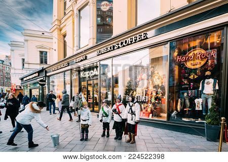 Helsinki, Finland - December 10, 2016: Star Singers Near Stockmann Department Store On Aleksanterinkatu Street. Children Sing Songs With Wishes Of Happiness And Passers-by Throw Coins To Them.