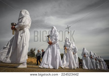 BERCIANOS, SPAIN- APRIL 3, 2015: Unidentified tourists walk with the antique brotherhood procession in Bercianos, Spain