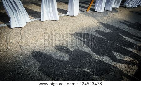 Tourist shadows taking photos and believers feet in easter traditional procession in bercianos de aliste brotherhood, Spain