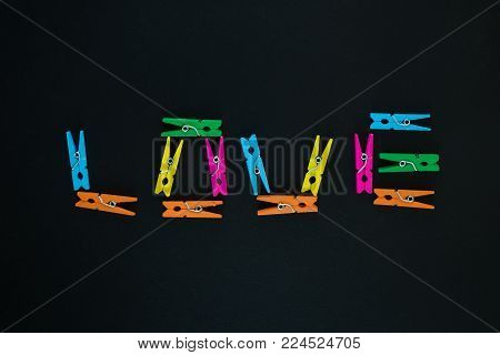 Love text made of colorful wooden clothes pegs on black background