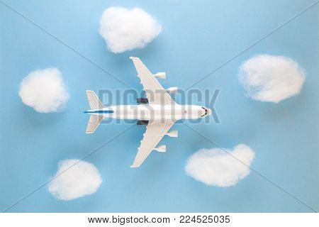Model aircraft plane flying through clouds. Minimal flat lay concept