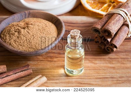 A bottle of cinnamon essential oil with cinnamon sticks and powder